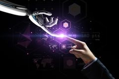 Robot and human hand over virtual projection. Artificial intelligence, future technology and business concept - robot and human hand with flash light and virtual royalty free stock photography