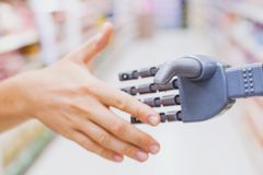 Robot and human hands in handshake, high tech in everyday life. Meet droid technology stock photography
