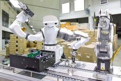 Robot industriel installant une puce dans la chaîne de production m image libre de droits