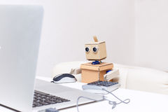 Free Robot Is Sitting At The Table And Working At A Laptop Royalty Free Stock Photography - 82927637