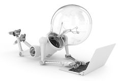 Robot lamp working on a laptop Stock Image