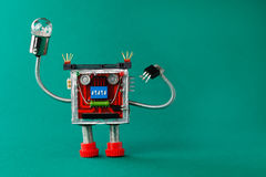 Robot with light bulb lamp in hand. Fun toy character on green background, copy space Stock Photo