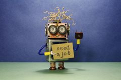 Robot looking for a job. The crazy unemployed toy robot holds cardboard announcement handwritten text Need a job. Blue royalty free stock image