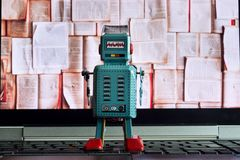 Robot looking at laptop screen with open books, artificial intelligence, big data and deep learning