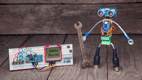 Robot made of parts of circuit boards with wrench near the debug. Board , on wood background Royalty Free Stock Photography