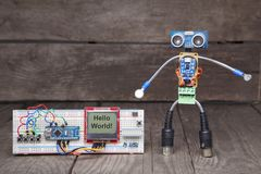 Robot made of parts of circuit boards with wrench near the debug. Board , on wood background Stock Image