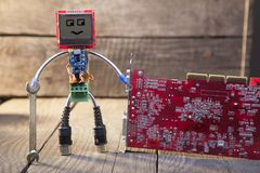 Robot made of parts of circuit boards with wrench, on wood backg Stock Photo
