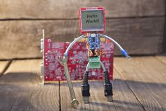 Robot made of parts of circuit boards with wrench, on wood backg Stock Photos
