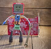 Robot made of parts of circuit boards with wrench, on wood background royalty free stock photo