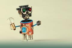 Robot meccanico con la lampadina Testa della plastica, occhi rossi verde colorato, mani elettriche del cavo, ruota del dente degl Fotografie Stock