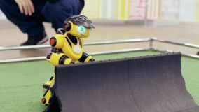 Robot moderne jaune ? l'exposition de nouvelles technologies L'homme commande le robot banque de vidéos