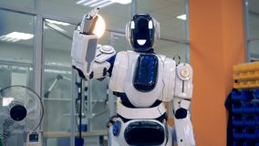 Robot moves its arm up, then puts it down. Happy droid moves its arm up and down, standing in a room stock video footage