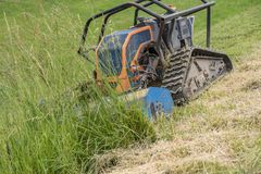 Robot mows meadow on hillside royalty free stock photo