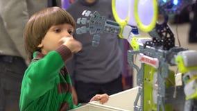 Robot och barn Pojke som söker efter dansroboten Hållande ögonen på robot för ungepojke att dansa Pojkeblick på robotic teknologi arkivfilmer
