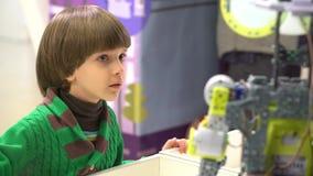 Robot och barn Pojke som söker efter roboten Hållande ögonen på robot för ungepojke Pojkeblick på robotic teknologi på utställnin stock video