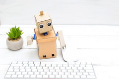 Robot - office worker and his workplace with a keyboard and mous. E Royalty Free Stock Image