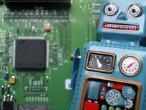 Robot with open circuit. A robot is in front of an open circuit board stock photo