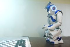 Robot plays Board games. A small robot with a human face and a humanoid body. Artificial intelligence-AI. Blue and white robot stock photography