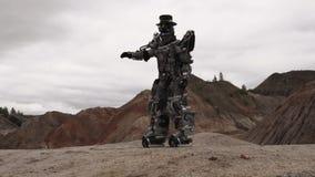 Robot que camina en un paisaje del desierto cantidad Robot de Android en el desierto de la montaña en tiempo nublado metrajes