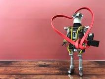 Robot que coloca y que lleva a cabo el corazón grande en manos Imagen de archivo libre de regalías