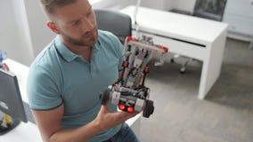 Robot que elabora enfocado del hombre joven en el trabajo