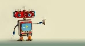 Robot rosso sorridente con la lampadina a disposizione Carattere gentile del giocattolo su un fondo di beige di pendenza Copi lo  Fotografia Stock Libera da Diritti