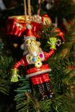 Robot Santa Christmas ornament on green Christmas tree with firetruck ornament in background stock photo