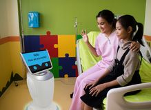 Robot service in medical talk with the patient at patient room i stock images