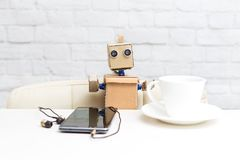 Robot sits at a table and drinks coffee and listened to music royalty free stock image