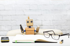 The robot sits at the table and holds a pen for writing Royalty Free Stock Image
