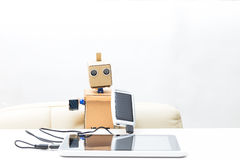 The robot sits at a table and holds a solar battery with a wire. And a tablet royalty free stock photo