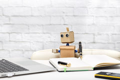 Robot is sitting at a table, holding a pen and looking at a lapt Royalty Free Stock Images