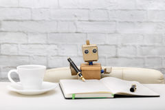 Robot is sitting at the table, working place: diary, pens, cups. Artificial Intelligence Stock Images