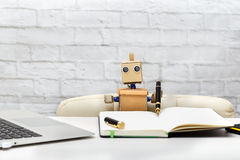 Robot is sitting at a table and writes a pen in a notebook Royalty Free Stock Photo