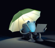 The robot sitting under umbrella and looks at the screen of the laptop Royalty Free Stock Images