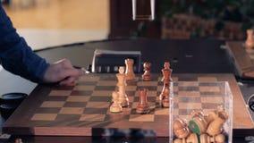 Robot som spelar schack med en man Räcka manipulatorflyttningar schacket och pressarna tangenten av kontrollklockan 4K arkivfilmer