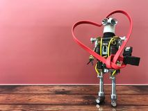 Robot standing and holding big heart in hands. Valentine's Day robot with romantic heart in hands made of cable. Empty space for text royalty free stock image
