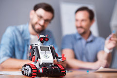 Robot standing o the table. Nice device. Selective focus of robot standing on the table while cheerful colleagues sitting in the background and working together Royalty Free Stock Photos