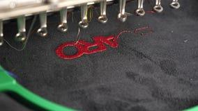 Robot szwalna maszyna Automatyczna szwalna maszyna automatyzująca maszyna haftuje wzór z czerwonymi niciami na czerni zbiory wideo