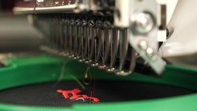 Robot szwalna maszyna Automatyczna szwalna maszyna automatyzuj?ca maszyna haftuje wz?r z czerwonymi niciami na czerni zdjęcie wideo