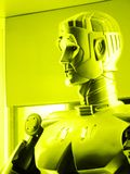 Robot talking. A conceptual image of a robot talking in the simple environment of a science lab.  Monochrome yellow photograph. Vertical format, nobody in Royalty Free Stock Photography