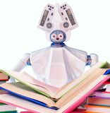 Robot teacher with book for kid. White plastic robotic device. Royalty Free Stock Photos