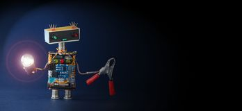 Robot technician lights the way into darkness. Friendly mechanic toy with lamp, red pliers on dark blue background Stock Photography