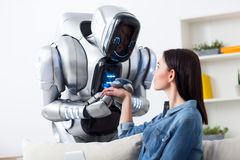 Robot tenant des mains de fille avec du charme Photo stock