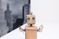 Robot tenant un fil et une diode électroluminescente sur la table blanche photo stock