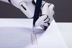 Robot Ticking Off Checkboxes On Document. Close-up Of A Robot Hand Ticking Off Checkboxes On Document With Pen royalty free stock images