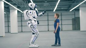 A droid and one girl touching hands, side view. Robot touches girl`s hand. 4K stock video footage