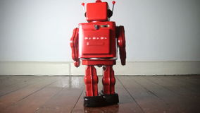 Robot toy. Red robot toy on wooden floor, marches into the frame