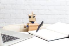 Robot trzyma pióro w swój ręce i pracuje za laptopem A Zdjęcie Royalty Free
