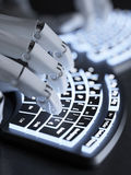 Robot typing on conceptual self-illuminated keyboard Royalty Free Stock Photo
